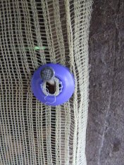 A plastic grommet that can be clamped onto the shade cloth with pliers.
