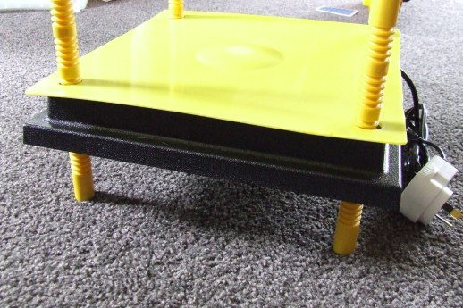 The heatplate gets a cover made from the yellow piece cut out of the brooder box lid. It was cut to size and four holes were cut in the corners to slip it over the heatplate legs.