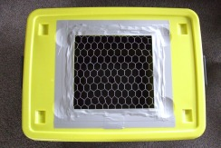 A hole was cut out of the lid and covered with wire netting for aeration and viewing.